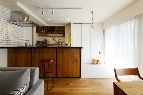 箕面にある「SQUARE」のキッチン。面材はオークを使用。アイアンのフレームとブラックの人造大理石天板が、白基調の空間を引き締めます。