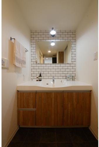 既存洗面台の扉にも玄関同様シートを貼り、鏡の背面にはキッチンと同じタイルを貼りました。
