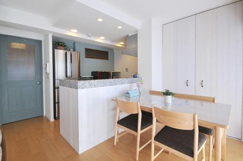 キッチンの吊戸棚を撤去してオープンキッチンに。カウンターのタイルや羽目板、アクセントカラーの壁がポイント。