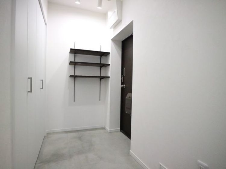 コンクリート仕上げのスタイリッシュな玄関。安らぎに満ちた生活空間を予感させてくれます。