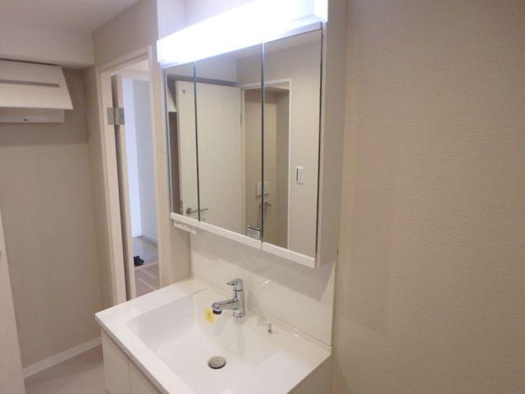 大きく見やすい三面鏡で清潔感ある洗面台は、身だしなみチェックや肌のお手入れに最適です。収納も多く、何かと物が増える場所だからこそスッキリと見映えの良い空間に拵えました。時間に余裕とゆとりを持たせます。