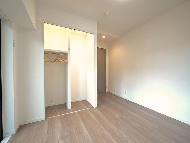 優しい色合いのフローリングが張られた約5.6帖の洋室