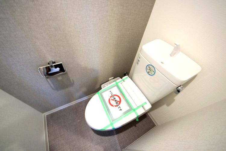 清潔感のある白い壁のトイレ