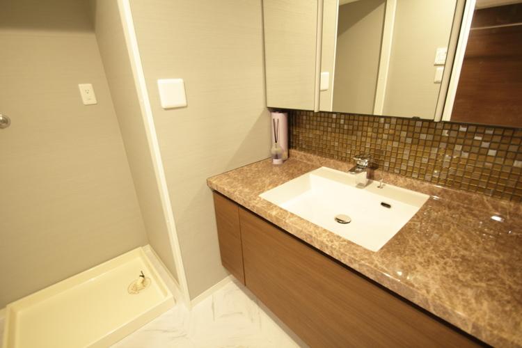 素材や照明にこだわった洗面室。三面鏡裏はすべて収納空間!排水位置を移動させ、洗面カウンター下のデッドスペースも収納スペースに。