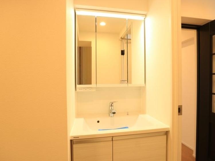 三面鏡の付いた洗面化粧台は、鏡面裏側にも機能的な収納を配置。スッキリと見映えの良い空間で、ゆったりと身支度ができます。