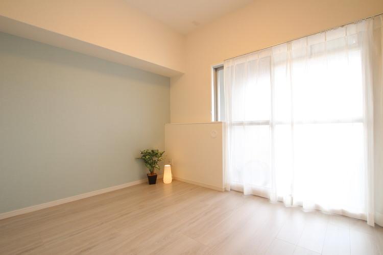 淡いカラーのアクセントクロスがポイントの洋室