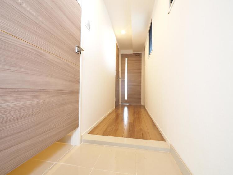 明るくコントラストのある、開放感と清潔感を兼ね備えた玄関。お子様が駆け込んでくる様子が想像できます。