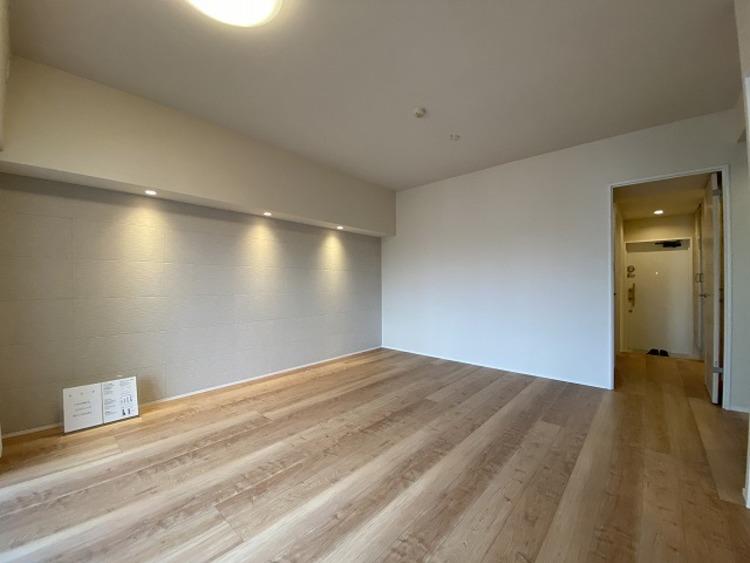 ナチュラルな木目調の床から木のぬくもりを感じられる広々としたリビングルーム。