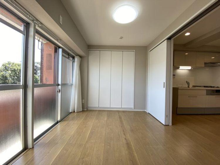 リビングと隣接の洋室は天井、フローリングと同じ色合いで揃えており、可動ドアを開くと広々とした空間に。