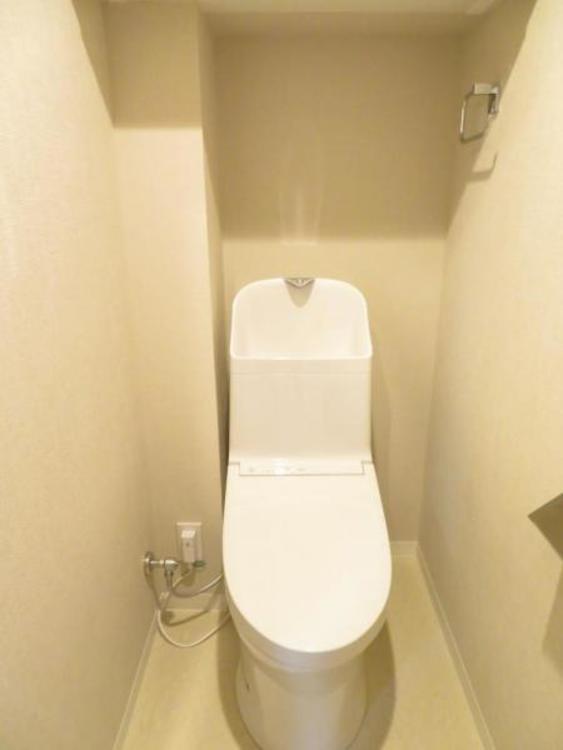 ウォシュレット機能付きのトイレ。上部の吊戸棚はトイレットペーパーなどのストックに便利!