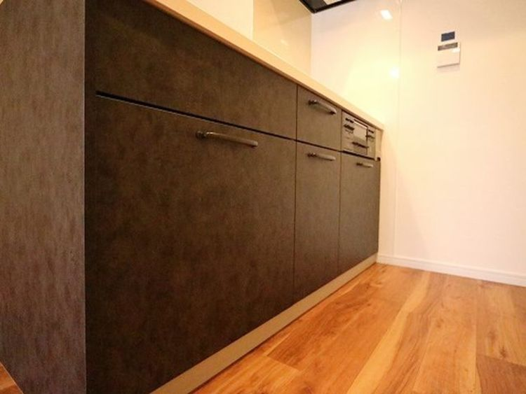 引出し収納や足下収納などにより、収納量がアップしているだけでなく、調理中、取り出しやすい位置に調理器具や食材等を収める細かい工夫がなされている幅広いシステムキッチンです。