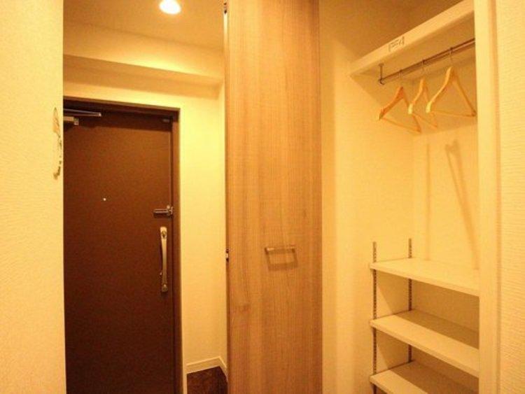 玄関には収納を設置。棚やハンガーパイプが付いた使いやすい設計でワードローブをスッキリ収納できます。