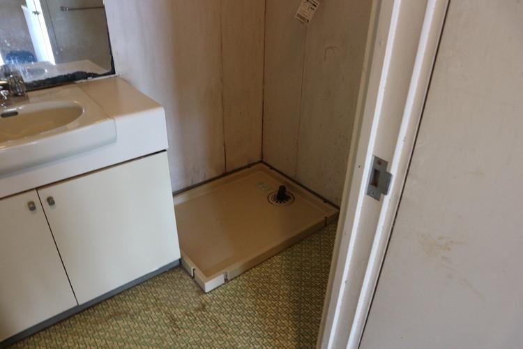 洗面所。右奥に洗濯機、隣に洗面台の配置。