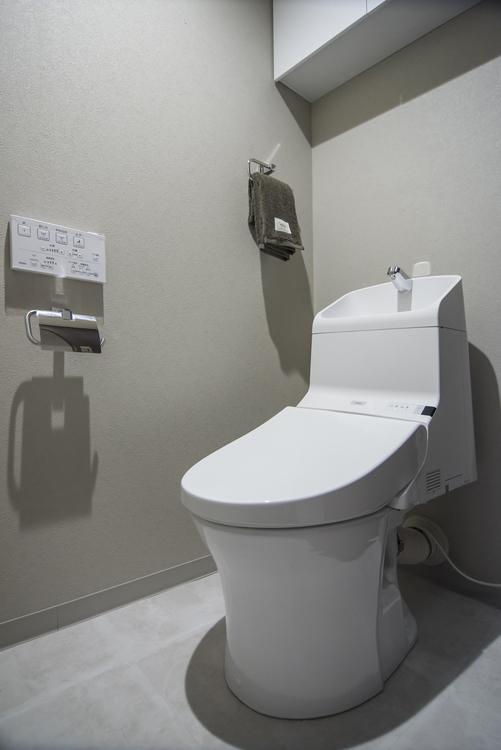 TOTO製洗浄便座を設置したトイレにはトイレットペーパーなどをしまうのに便利な吊戸棚を備え付けています