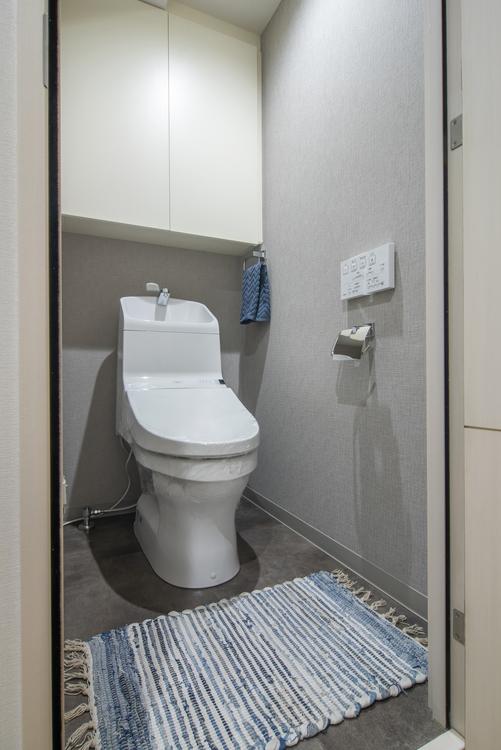 トイレットペーパーなどをしまうのに便利な吊戸棚を備え付けたトイレは、TOTO製洗浄便座付きトイレを新規設置