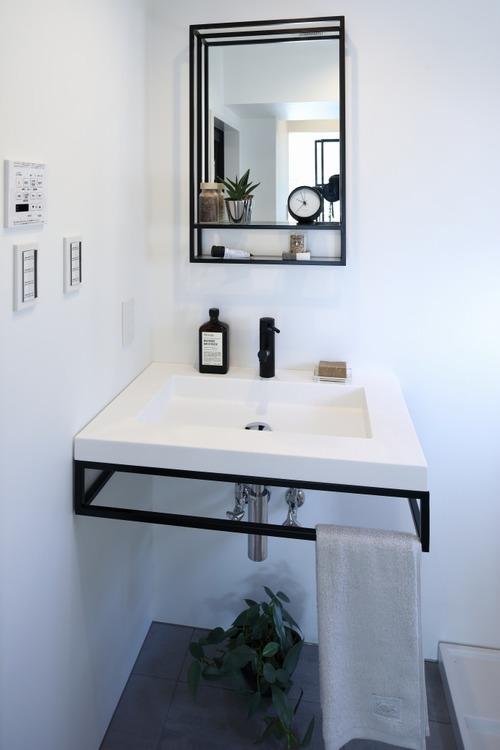 洗面台に設置された黒のフレームはタオル掛けになっていて、スタイリッシュながら機能も兼ねそろえています。