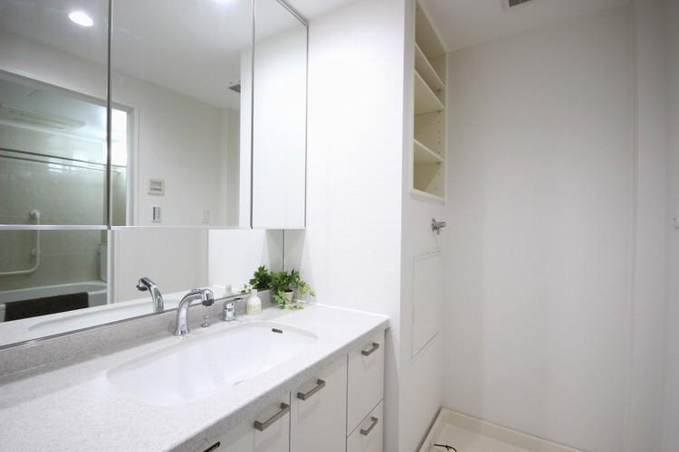 【三面鏡の洗面台】見やすくて使いやすい三面鏡を備えた洗面台は、お肌のお手入れなどのスキンケアを施すときに適しています。収納スペースも多く設置。シンプルな空間を彩っています。