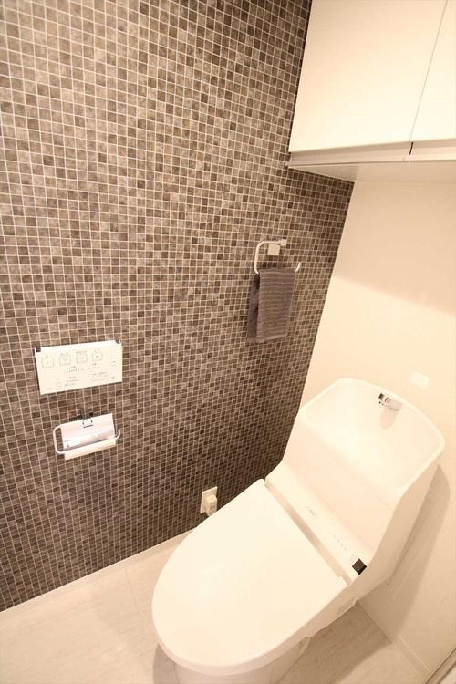 トイレ壁面には、タイル調のクロスを採用。おしゃれな空間です