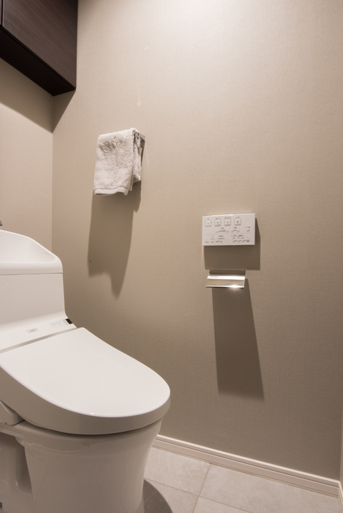 TOTO製の洗浄便座を設置したトイレには、トイレットペーパーなどをしまうのに便利な吊戸棚付きです