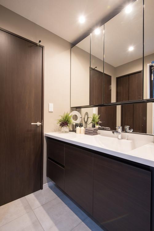 身だしなみを整えるのに便利な大型三面鏡のついた、ゆったりした広さのあるLIXL製洗面化粧台を設置
