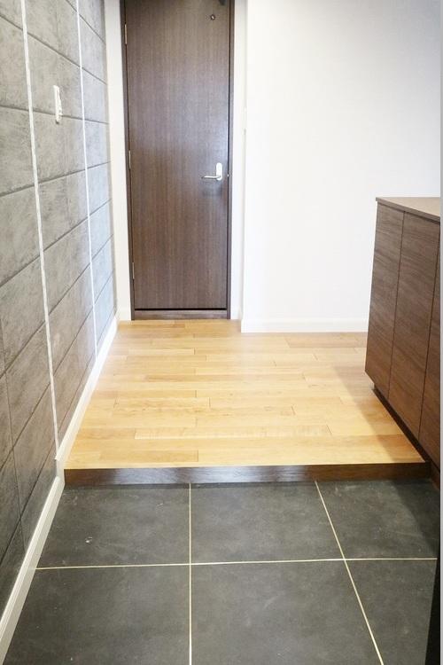 壁面をグレーのタイル調のクロスが貼られた玄関フロアには、省エネ効果を期待できる人感センサー付き