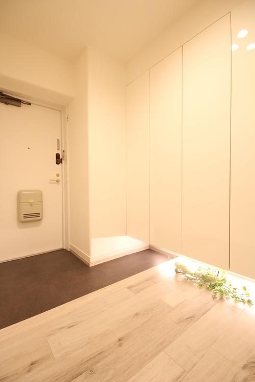 住まいの第一印象を決める玄関スペースには間接照明とホワイト鏡面の下足入を使用し、高級感と清潔感を演出