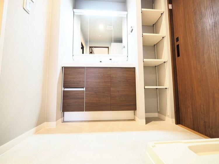 キッチンからも出入り出来る洗面所には、大容量のベースキャビネットと全収納型のミラーキャビネットを備える洗面化粧台。タオルなどをコンパクトに収納できる棚も標準装備。