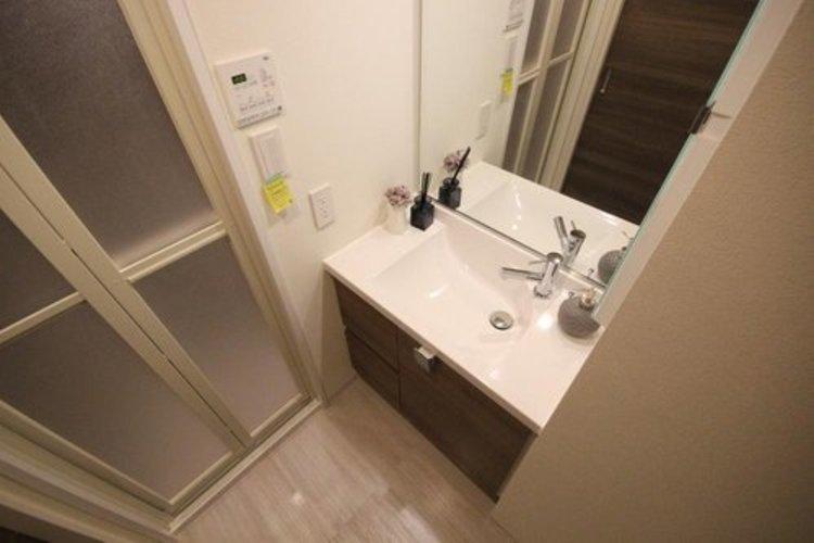 【洗面台(同社施工事例)】大きく見やすい三面鏡で清潔感ある洗面台は、身だしなみチェックや肌のお手入れに最適です。何かとに物が増える場所だからこそ、スッキリと見映えの良い空間に拵えました。