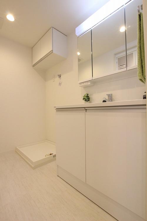 白を基調とした明るく清潔感のある洗面室。鏡の裏には、ハブラシやコンタクト用品をしまっておけます
