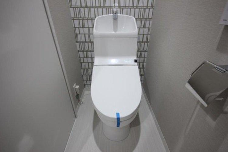 白を基調とした清潔感の高いお手洗い。上部に収納もついておりますので、とても便利です