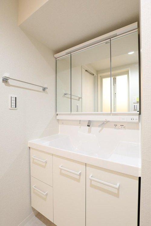 三面鏡となっている洗面台には、収納もしっかりと備わっております。