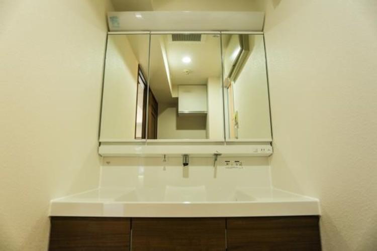 <三面鏡の洗面台 :洗面台>見やすくて使いやすい三面鏡を備えた洗面台は、お肌のお手入れなどのスキンケアを施すときに適しています。収納スペースも多く設置。シンプルな空間を彩っています。