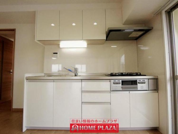 白い清潔感のあるシステムキッチンは、収納もたっぷり!