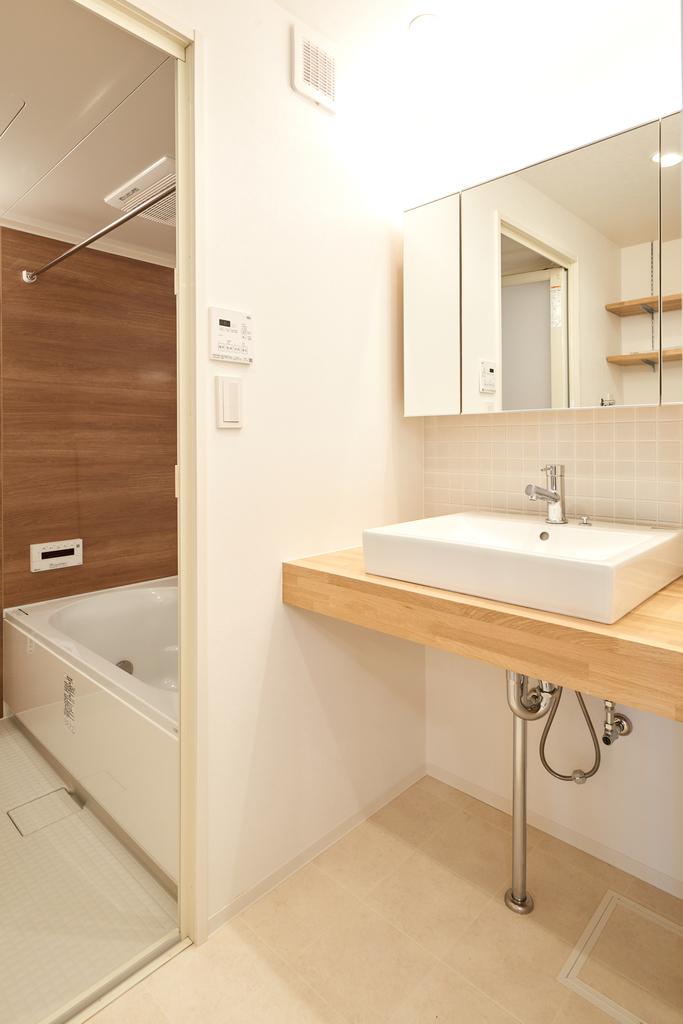 上部の間接照明が暖かいシンプルな洗面台。3面鏡の裏には小物を収納できます。