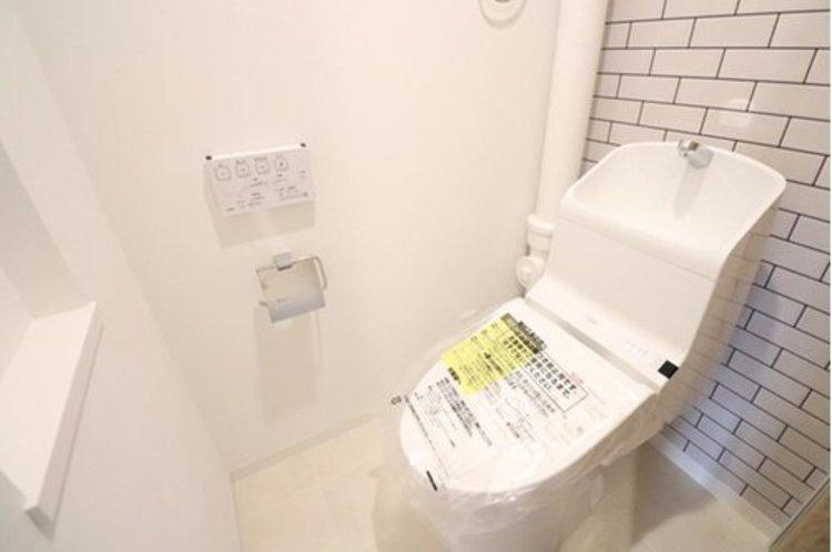 トイレの背面はまるでタイルのようなクロスを貼りました。一面貼るだけでお洒落な空間に。