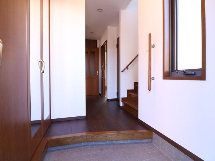 ご家族を見送り、そして迎え入れる空間にふさわしい明るい玄関。手摺を設置しております。