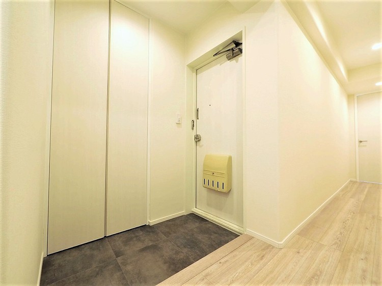 白い清潔感のある玄関には天井までの収納スペースがあります