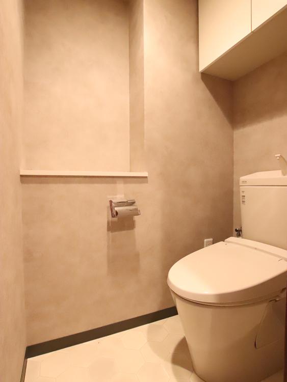 新品のトイレ。上部に棚があり消耗品の収納場所も確保できます
