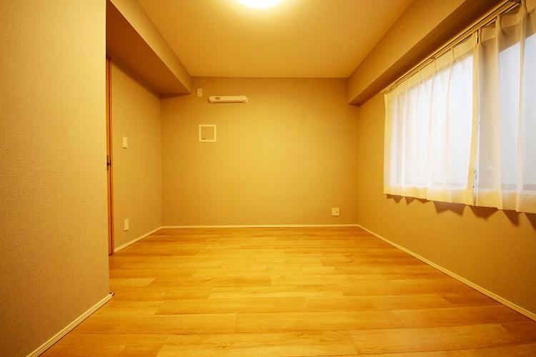 優しい色合いのフローリングが張られた約5.5帖の洋室