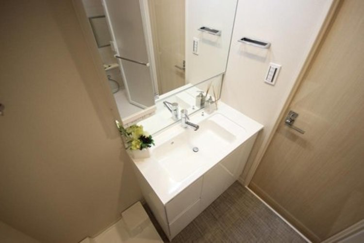 大きく見やすい三面鏡で清潔感ある洗面台は、身だしなみチェックや肌のお手入れに最適です。何かとに物が増える場所だからこそ、スッキリと見映えの良い空間に拵えました。 ≫