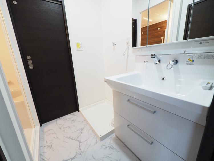 目線に合わせた三面鏡付洗面化粧台を採用しました。三面鏡の裏側には収納棚を確保。