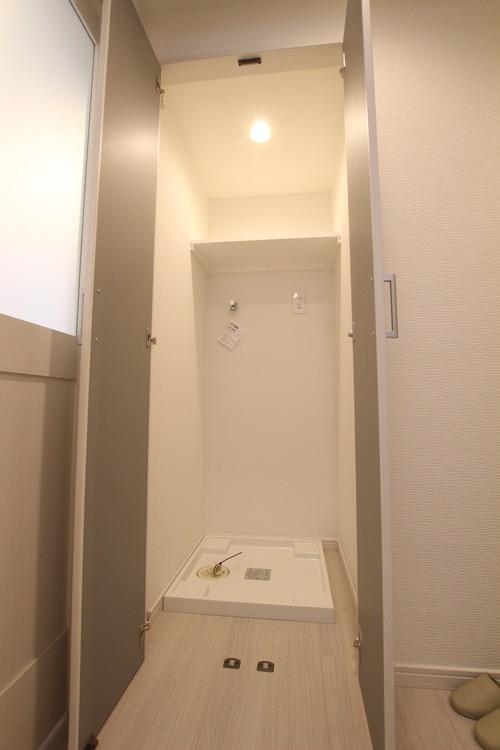 洗剤や洗濯ネットなどが老いておける吊戸棚付きの洗濯機置場