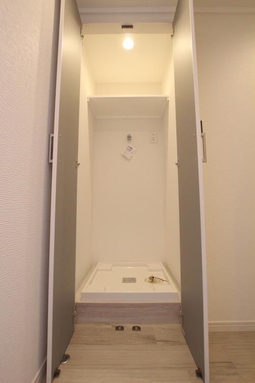洗濯機置場は廊下にありますが、扉がついているので生活感を隠すことができます