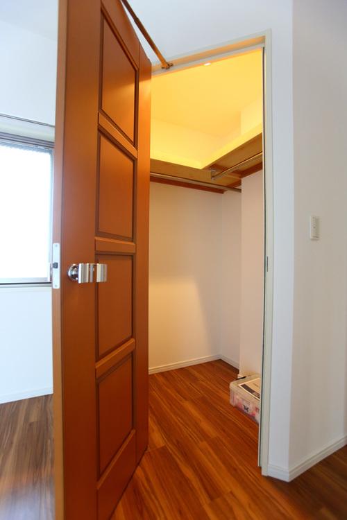 ブラウンのおしゃれな扉を開けるとクローゼットがあります。お洋服をたくさん収納できます