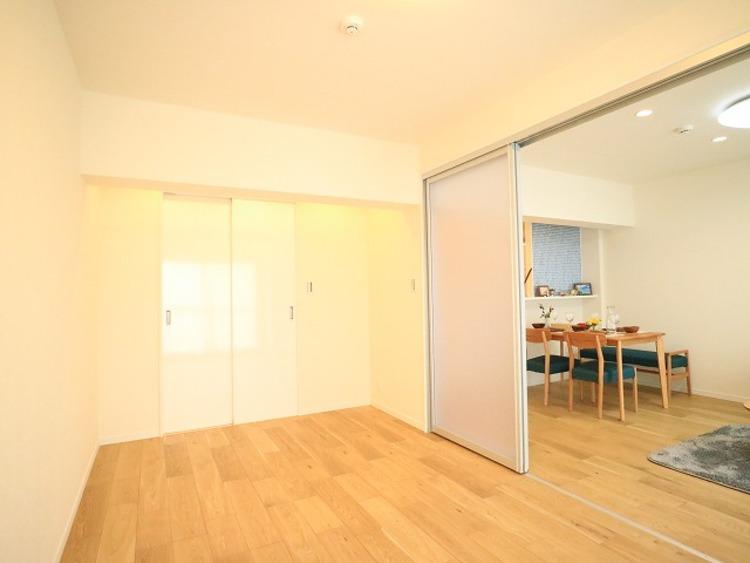 リビングと隣接の洋室は天井、フローリングと同じ色合いで揃えており、可動ドアを開くと広々とした空間になります。家族構成の変化にも柔軟に対応するための工夫をいたしました。