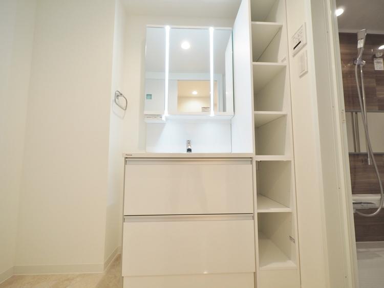 目線に合わせた三面鏡付洗面化粧台を採用しました。三面鏡の裏側には収納棚を確保。収納棚を多く設けており、脱衣スペースを広く確保しております。