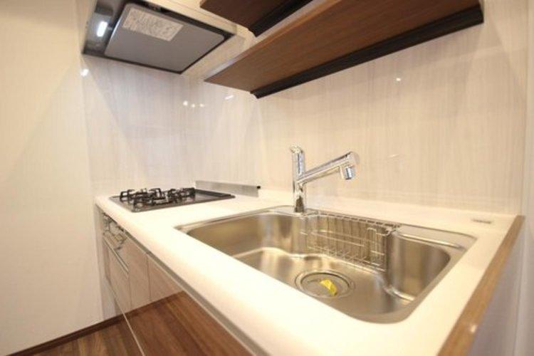 明るい自然光が入る作業スペースを多くとった壁付けキッチン採用。夫婦揃ってキッチンに立っても調理がしやすく、家事をしながら会話も弾みます。食器類もすっきりと片付く収納力。 ≫