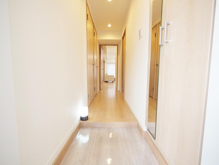 上質感漂う玄関と廊下。居住者の帰り、訪れる方を優しく迎える・安らぎに満ちた生活空間を予感させる。