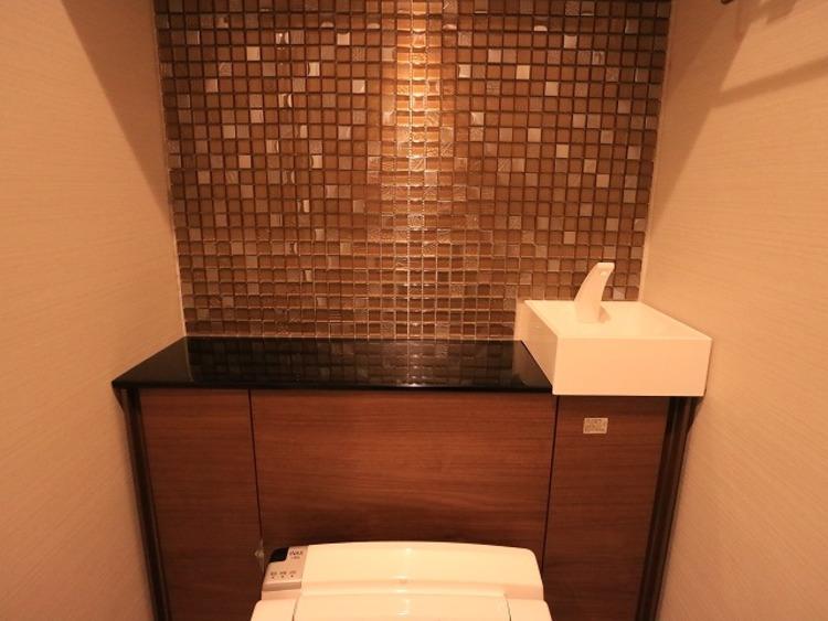 タイル張りで高級感溢れるトイレ。落ち着いた空間で安らぎのひとときをお過ごしいただけます。