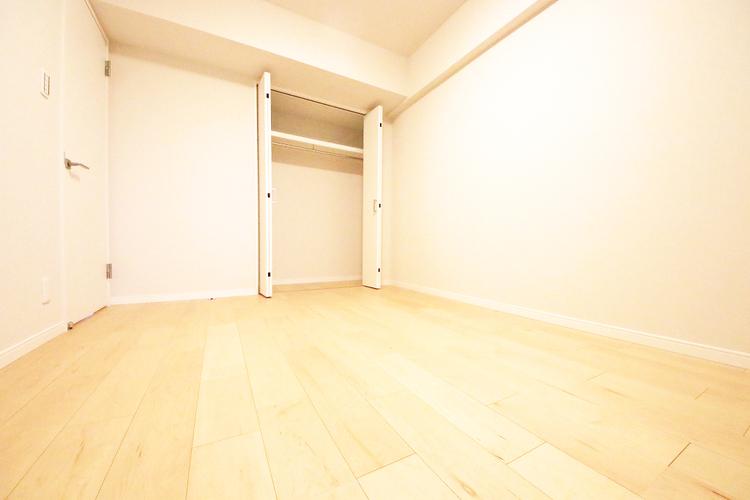 優しい色合いのフローリングが張られた約6.1帖の洋室
